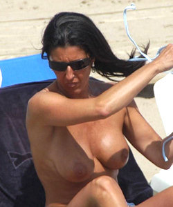 Hot topless chicks on the beach show their large tits