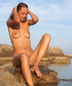 Nude nudist girl on the rock