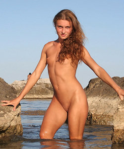 Girl nude on the rock in the sea