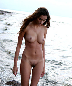 Sexy breasted babe walks on the beach